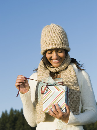 Mixed race woman opening gift