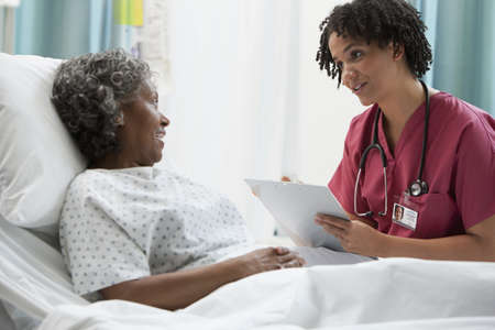 African nurse talking with hospital patient LANG_EVOIMAGES