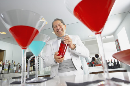 Hispanic host mixing martini cocktails at party