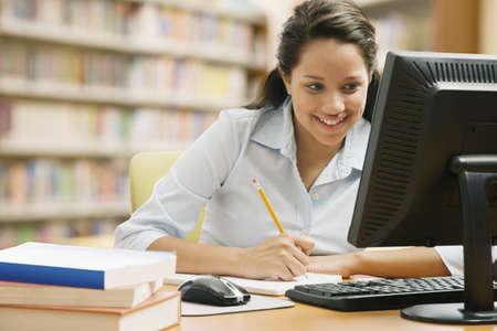 Hispanic girl writing in school library