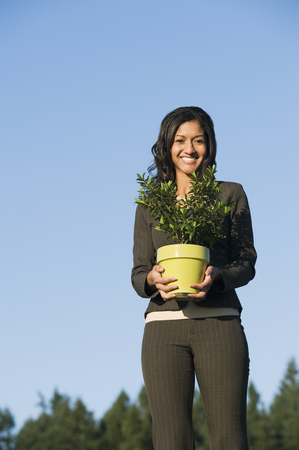Mixed race businesswoman holding potted plant