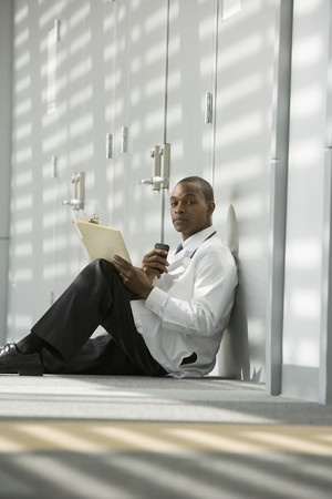 African doctor sitting on floor dictating medical record into recorder LANG_EVOIMAGES