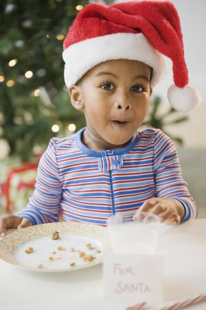 African American boy pointing to eaten cookies by For Santa sign