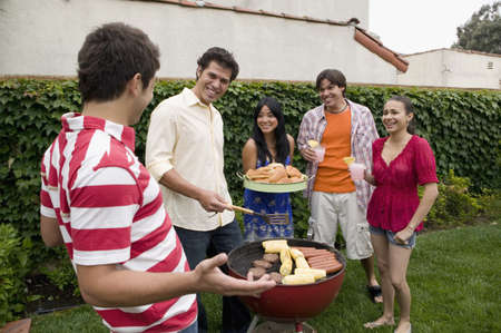 Hispanic friends having barbecue LANG_EVOIMAGES