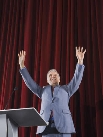 Businessman with arms raised behind podium
