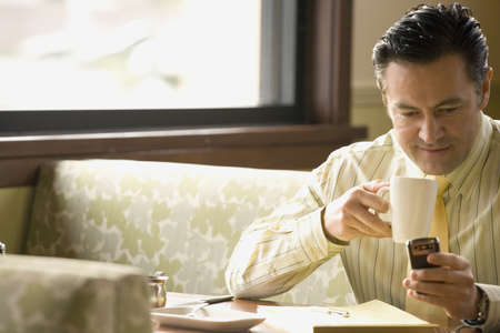 Hispanic man drinking coffee and checking messages LANG_EVOIMAGES