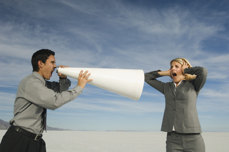 Hispanic businessman yelling at businesswoman through megaphone