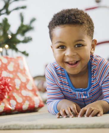 African American boy laying on floor by Christmas tree