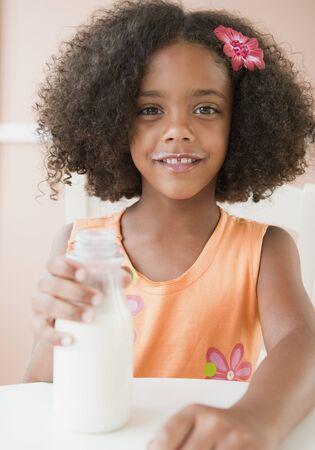 Mixed race girl drinking milk