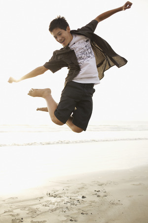 Mixed race boy jumping on beach