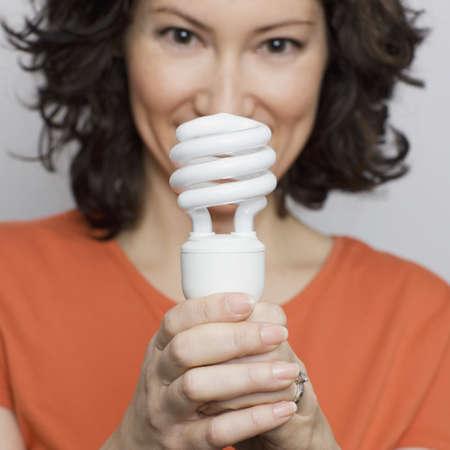 Hispanic woman holding energy efficient light bulb