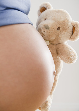 Pregnant Hispanic woman holding teddy bear LANG_EVOIMAGES