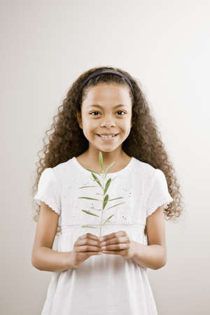 Mixed Race girl holding plant LANG_EVOIMAGES