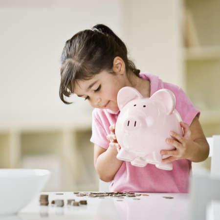 Indian girl holding piggy bank LANG_EVOIMAGES