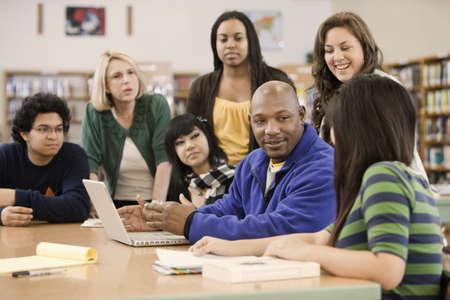 Knihovník pomáhá studentům ve školní knihovně