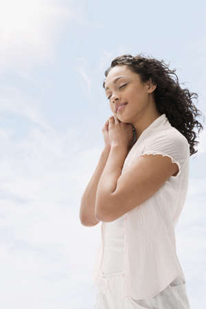 Mixed race teenage girl standing outdoors with eyes closed