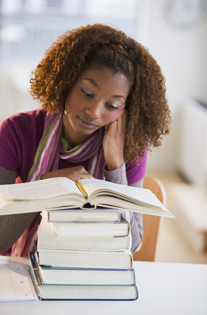 Mixed race woman looking at stack of books LANG_EVOIMAGES