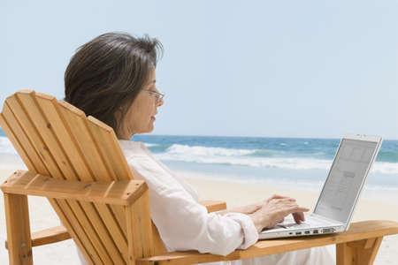 Mujer hispana escribiendo en la computadora portátil LANG_EVOIMAGES