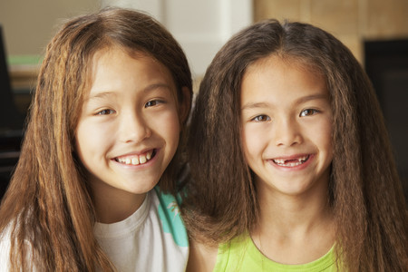 Mixed race sisters smiling LANG_EVOIMAGES