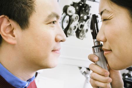 Asian female optometrist examining patient
