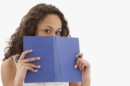 Mixed race teenage girl hiding behind book