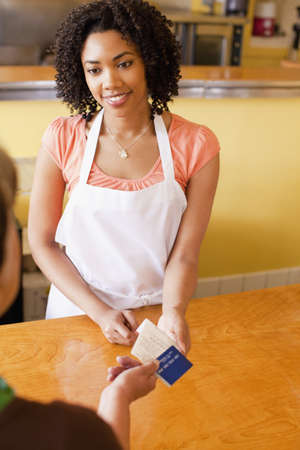 African American woman taking credit card from customer