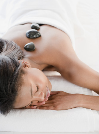 Mixed race woman having hot stone therapy