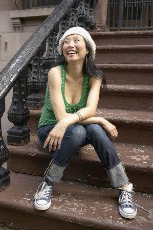 Asian woman sitting on front steps LANG_EVOIMAGES