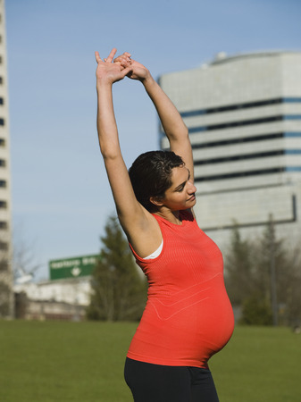 Pregnant Middle Eastern woman stretching LANG_EVOIMAGES