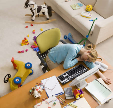 Hispanic woman sleeping at desk surrounded by toys LANG_EVOIMAGES