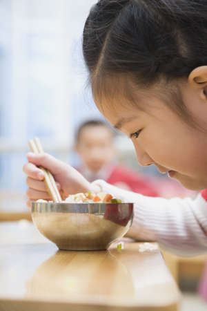 Chinese girl looking at food in bowl