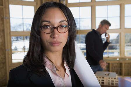 Mixed race businesswoman holding blueprints