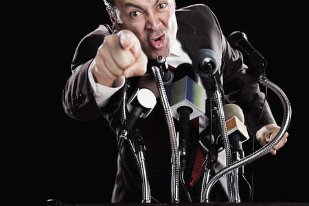 Angry Hispanic man pointing at podium with microphones LANG_EVOIMAGES