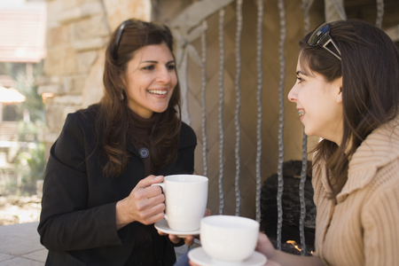 Middle Eastern mother and daughter drinking coffee