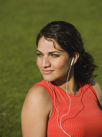 Middle Eastern woman listening to music in park