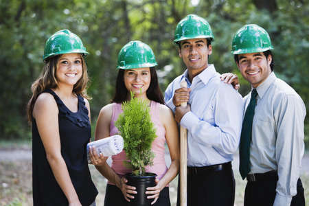 Hispanic business people planting trees in forest LANG_EVOIMAGES