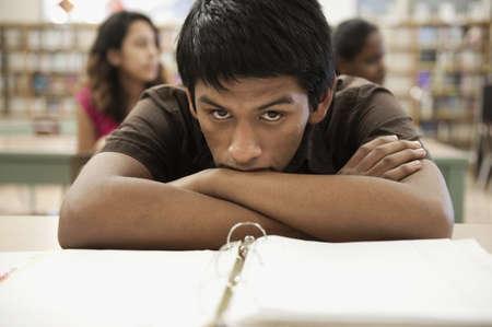Naneštěstí hispánský dospívající chlapec se nudil ve školní knihovně LANG_EVOIMAGES