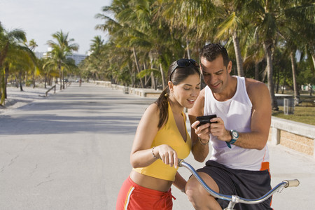 Hispanic couple on bicycles looking at cell phone LANG_EVOIMAGES