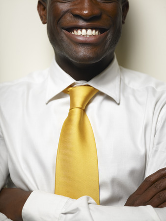 Smiling Black businessman with arms crossed LANG_EVOIMAGES