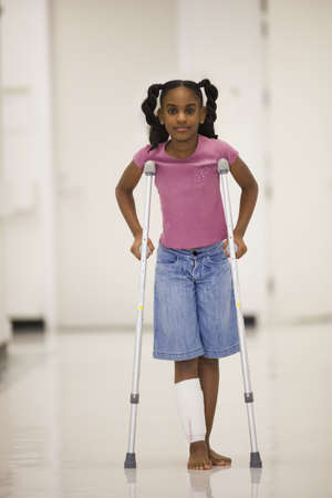 African American girl walking on crutches LANG_EVOIMAGES