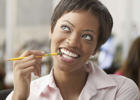 African woman biting eraser of pencil and looking up LANG_EVOIMAGES