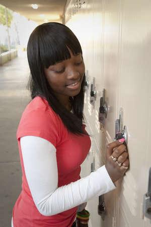 African teenage girl opening school locker LANG_EVOIMAGES