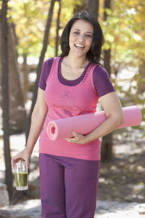 Mixed race woman holding yoga mat and beverage LANG_EVOIMAGES