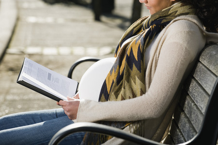 Pregnant Middle Eastern woman reading on park bench LANG_EVOIMAGES