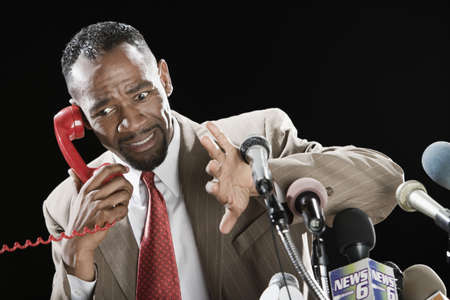 Worried African man talking on telephone at podium with microphones LANG_EVOIMAGES