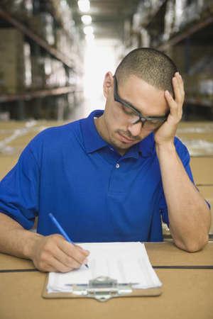 Hispanic man completing paperwork in warehouse LANG_EVOIMAGES