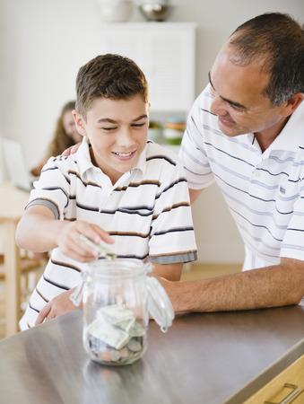Hispanic father watching son put money into jar LANG_EVOIMAGES