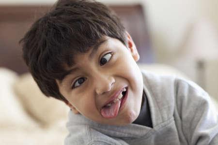 Niño hispano haciendo una cara y sacando la lengua LANG_EVOIMAGES