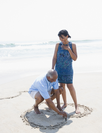 Black man drawing heart on beach for wife LANG_EVOIMAGES