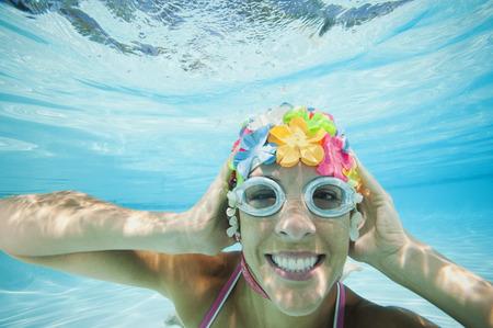 Hispanic woman in retro swimming cap underwater in swimming pool LANG_EVOIMAGES